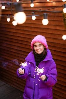 Une fille caucasienne s'amuse en hiver dans la rue avec des cierges magiques à la main, souriant de bonheur avec ...