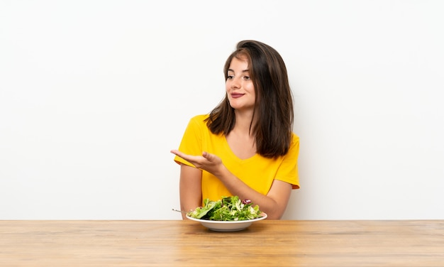 Fille caucasienne avec salade tendant les mains sur le côté pour inviter à venir