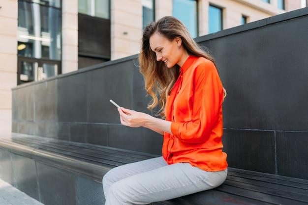 Une fille caucasienne souriante est assise dans la ville et utilise un smartphone dans ses mains