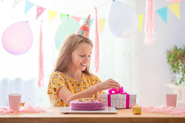 Fille caucasienne sourit rêveusement et regarde le gâteau arc-en-ciel d'anniversaire. fond coloré festif avec des ballons. fête d'anniversaire et concept de souhaits.