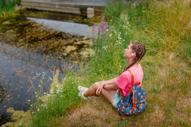 Une fille caucasienne avec des taches de rousseur et dans un t-shirt rose est assise sur l'herbe. une étudiante sourit et profite du beau temps d'été.