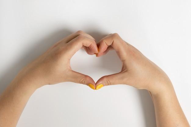 Fille caucasienne tenant un symbole de forme de coeur avec ses doigts de mains