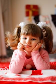 Fille caucasienne triste dans un pull rose se trouvant avec ses mains sous les joues sur le blacket de noël.