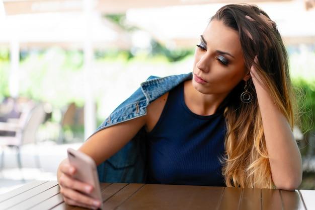 Une fille caucasienne triste et solitaire est assise dans un café d'été ouvert