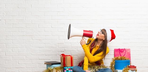 Fille célébrant les vacances de noël criant à travers un mégaphone pour annoncer quelque chose