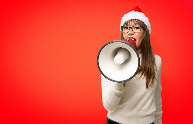Fille avec célébrer les vacances de noël en criant à travers un mégaphone