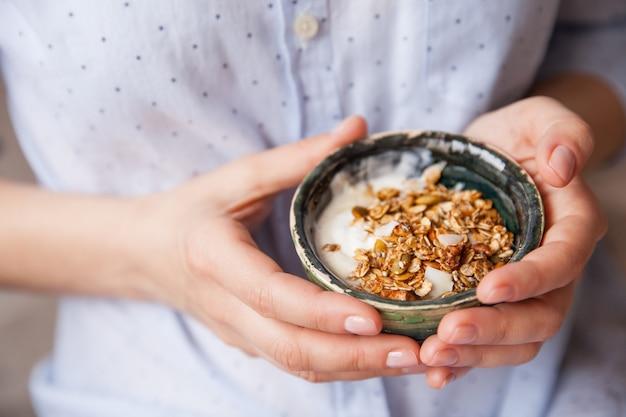 Fille avec des céréales de yaourt avec de l'avoine de graines de citrouille de noix dans un bol