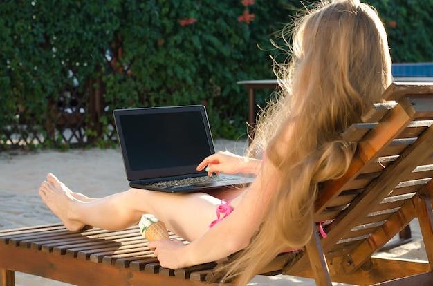 Fille sur une chaise longue avec un ordinateur portable sur ses genoux