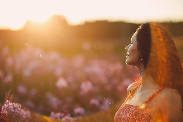 Fille sur le champ de fleurs sally en fleurs au coucher du soleil. fleurs et femme lilas. mise au point sélective douce avec sunflare.