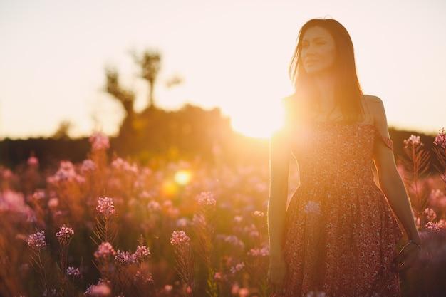 Fille sur le champ de fleurs sally en fleurs au coucher du soleil. fleurs et femme lilas.