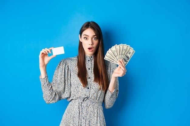 Fille chanceuse excitée montrant une carte de crédit en plastique et un dollar en argent, haletant étonné, achetant quelque chose de cher, debout sur le bleu.