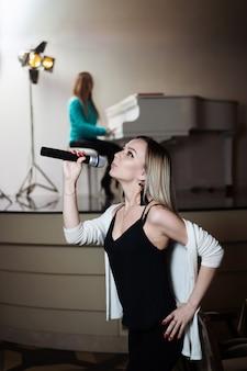 Une fille chante dans un restaurant et derrière son collègue joue du piano.