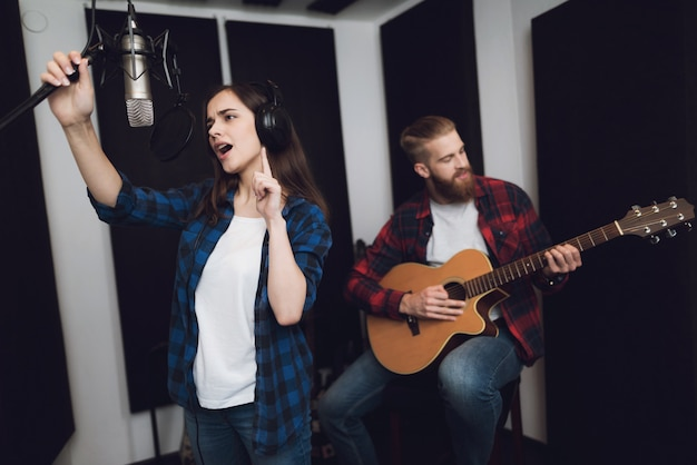 La fille chante pendant que le gars joue de la guitare.