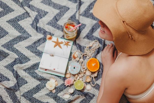 Fille avec chapeau et agenda sur la serviette de plage