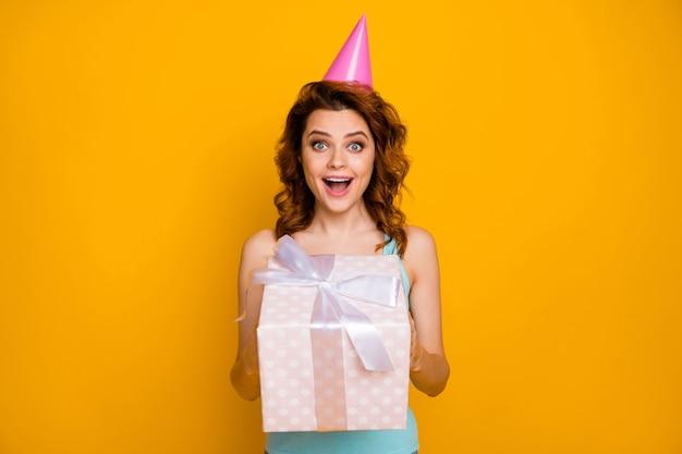 Fille avec chapeau de fête et cadeau isolé sur orange