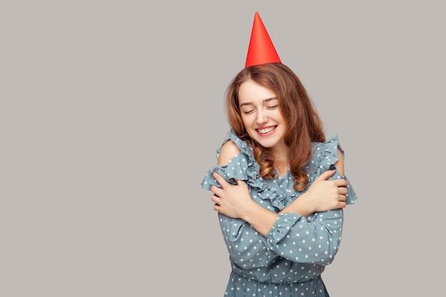 Fille avec chapeau de fête s'embrassant, souriante satisfaite de son apparence de beauté