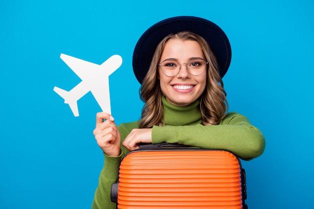 Fille avec chapeau et lunettes restant avec valise et avion