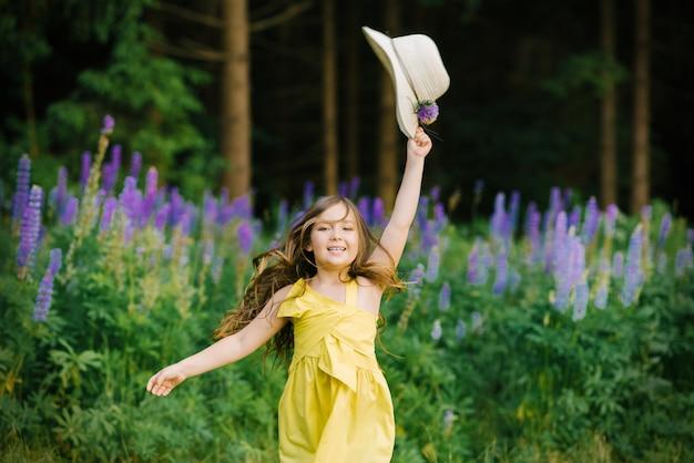 Fille avec un chapeau à la main souriant sautant dans un champ de lupin