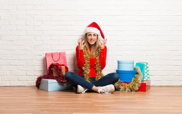 Fille avec un chapeau de noël et de nombreux cadeaux célébrant les vacances de noël agacé en colère