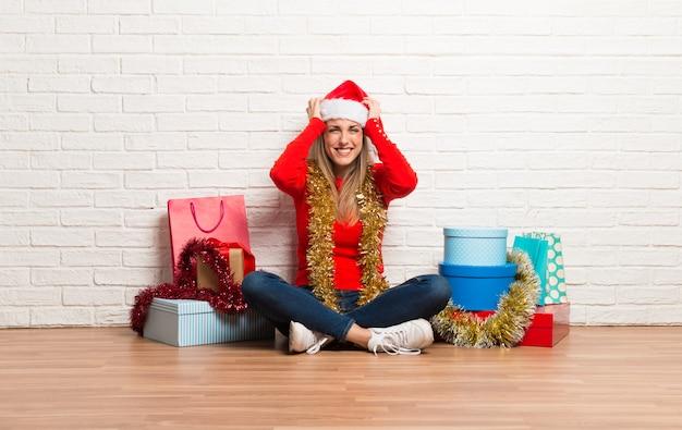 Fille avec un chapeau de noël et de nombreux cadeaux célébrant les vacances de noël malheureuses