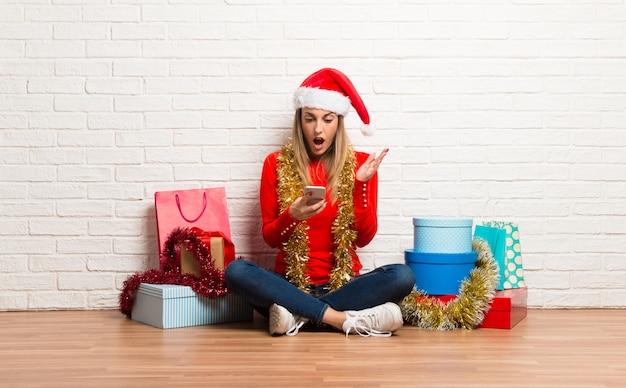 Fille avec un chapeau de noël et de nombreux cadeaux célébrant les vacances de noël parlant à mobile