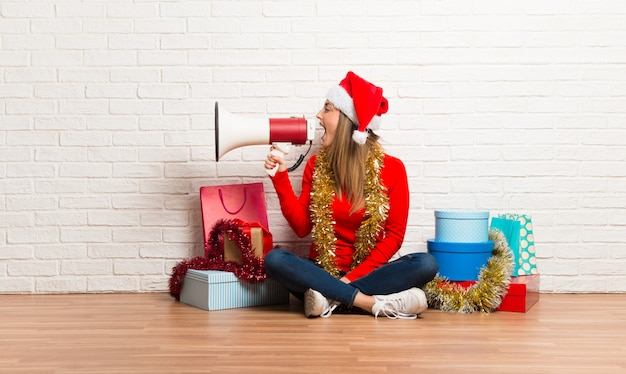 Fille avec un chapeau de noël et de nombreux cadeaux célébrant les vacances de noël tenant un mégaphone