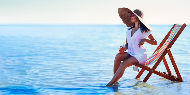 Fille en chapeau de soleil et tunique assise sur la chaise de plage au bord de la mer tout en tenant des vacances d'été cocktail