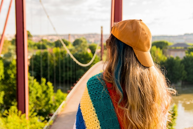 Fille avec chapeau de veste de sport doré et couverture multicolore face au pont rouge à l'aube. concept de mode de vie