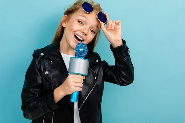 Fille charismatique excitée chantant en karaoké avec deux microphones sur un fond de mur bleu