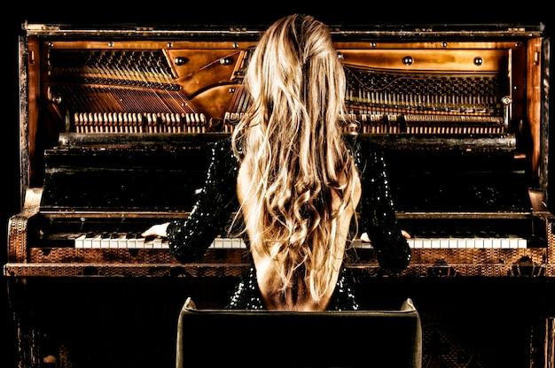 Fille charmante aux cheveux longs luxueux joue d'un piano rétro