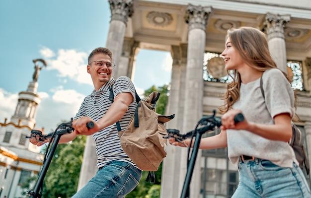 Une fille charmante et un gars attrayant sur des scooters électriques.