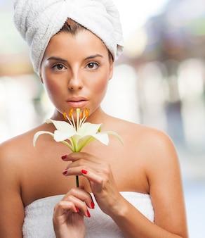 Fille de charme avec une peau parfaite dans une serviette avec lily