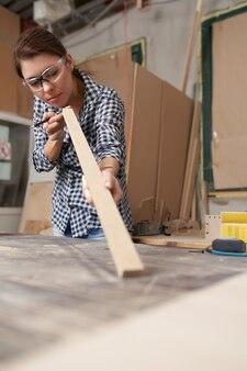 Fille charpentier dans des verres avec dos en bois et crayon dans ses mains en atelier