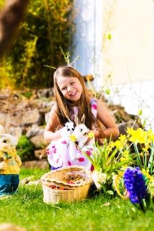 Fille sur la chasse aux oeufs de pâques avec vivant lapin de pâques
