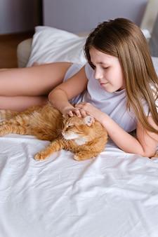 Une fille avec un chat roux se trouve sur un lit blanc. une jeune fille caresse un chat roux en position couchée sur une feuille blanche