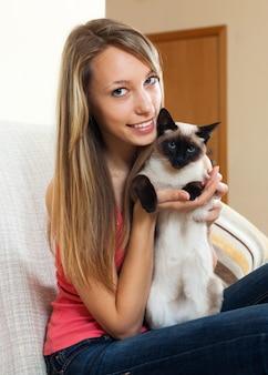 Fille avec un chat siamois dans la chambre