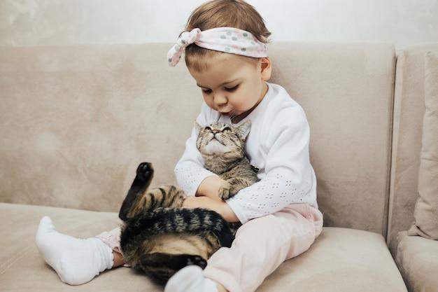 Fille avec un chaton dans les mains assis sur le canapé dans le salon