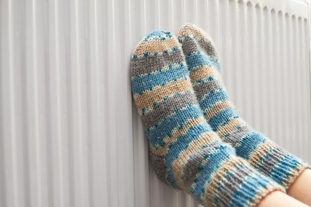 Fille en chaussettes de laine réchauffe ses pieds sur le radiateur