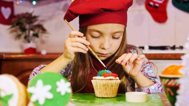 Une fille de chef gaie décorant un petit gâteau. ambiance d'avant noël