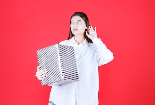 Fille en chemise blanche tenant une boîte-cadeau en argent, regardant et appelant quelqu'un