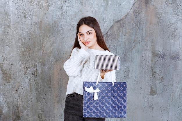 Fille en chemise blanche tenant une boîte-cadeau en argent et un sac à provisions bleu et à la confusion et réfléchie à faire un choix.