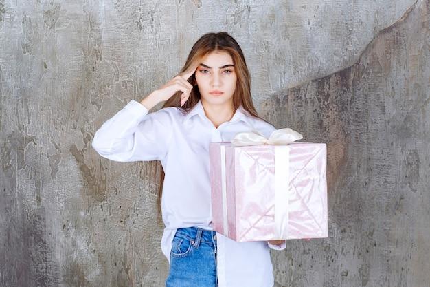 Fille en chemise blanche tenant une boîte-cadeau rose enveloppée d'un ruban blanc et semble confuse et hésitante.