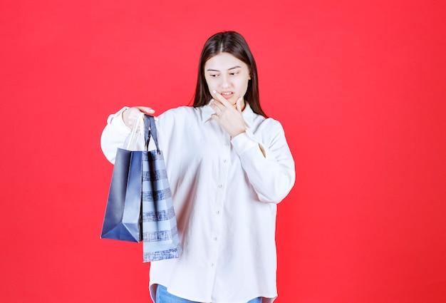 Fille en chemise blanche tenant plusieurs sacs à provisions et semble confuse et hésitante