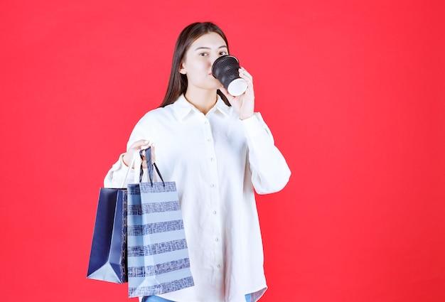 Fille en chemise blanche tenant plusieurs sacs à provisions et une tasse de café à emporter noire