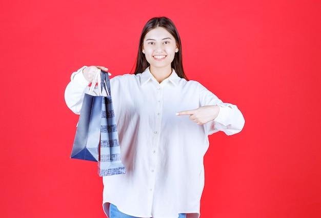 Fille en chemise blanche tenant plusieurs sacs à provisions