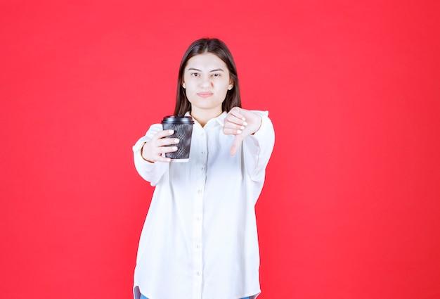 Fille en chemise blanche tenant une tasse de café à emporter noire et montrant le pouce vers le bas