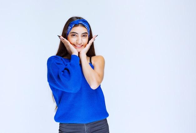 Fille en chemise bleue donnant des poses neutres et gaies.