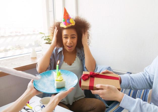 Fille en chemise bleue fête son anniversaire aujourd'hui. ses amis lui ont fait une surprise. ils tiennent un cadeau et un morceau de gâteau avec une bougie dessus. le gilr d'anniversaire tient le chapeau avec ses mains.