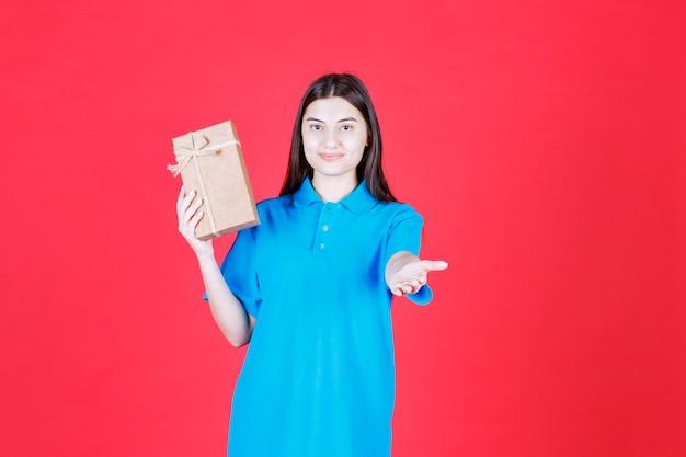 Fille en chemise bleue tenant une mini boîte-cadeau en carton et appelant quelqu'un à s'approcher et à le prendre