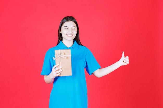 Fille en chemise bleue tenant une mini boîte-cadeau en carton et se sentant positive
